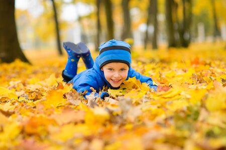 Junge in blauer Jacke und Hut, der in einem Herbstpark einen Arm voll gelber Ahornblätter harkt