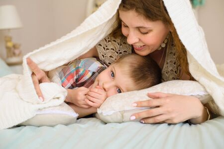 Mom gently looks at her son. they lying on bed covered with bedspread in bright bedroom. She hugs child carefully