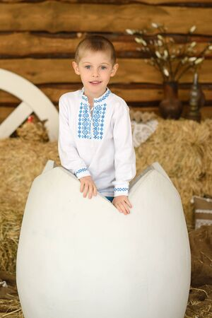 beautiful boy peeks out of huge decorative egg on background of pile of hay
