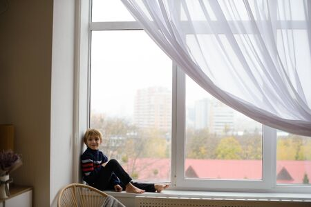 boy sits on windowsill, near window glass, wants to walk on street, but in world there is coronavirus pandemic, and he remains at home in quarantine
