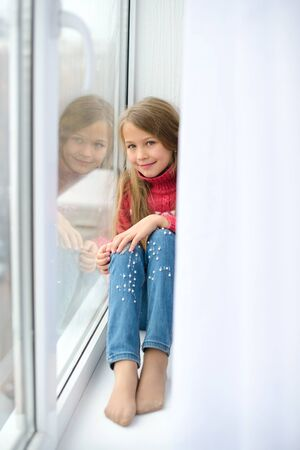 girl sits on windowsill, near windowpane, she wants to walk on street, but in world there is coronavirus pandemic, and she remains at home in quarantine