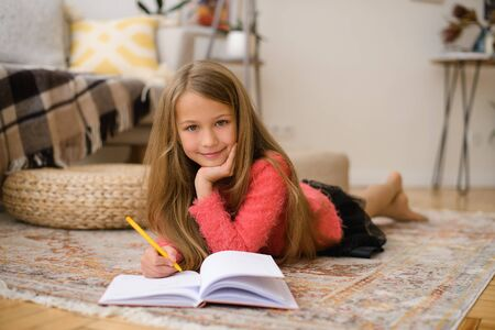 during worldwide coronavirus pandemic, girl learns school curriculum in apartment without leaving home. Lies on floor and writes in notebook with pen