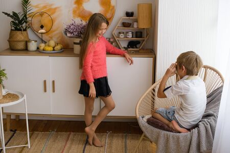 boy sitting in wicker chair photographs his sister, who is standing posing near white bedside table, in morning at home. Foto de archivo