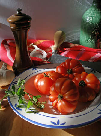 Tomatoes, pepper mill andolive oil in the kitchen in the sunset light Stock Photo