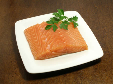 raw salmon steak with parsley on a small plate