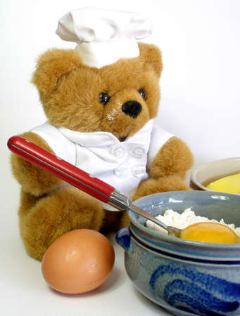 Teddy bear is baking a cake. I don't know what sort. He should remove the flour on his face.