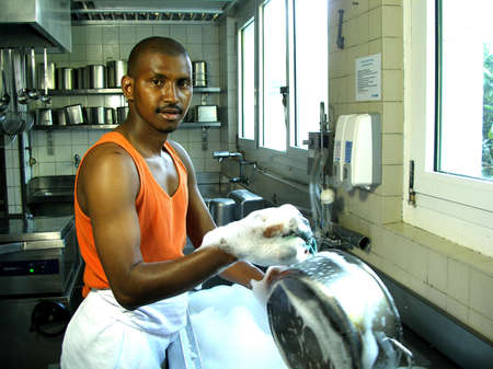 African guy is washing a pot