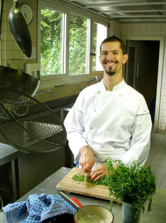 Cis slicing tarragon on a wooden cutting board in the kitchen