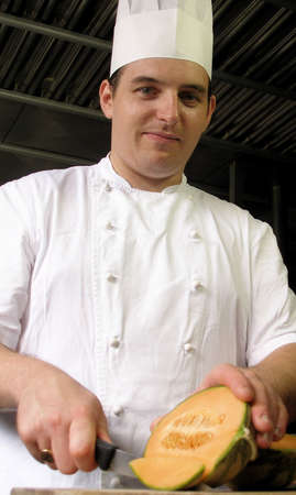 Chef is slicing a cantaloupe on the cutting board Stock Photo