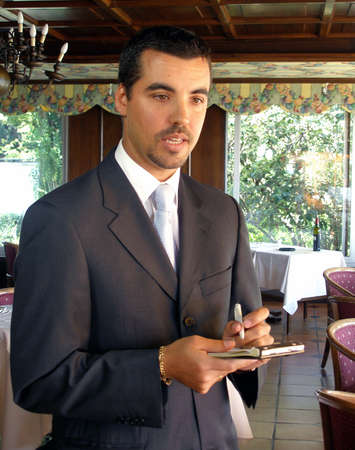 Maitre D is taking an order in the dining room