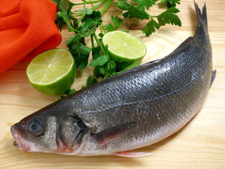 Sea bass on the cutting board with lime