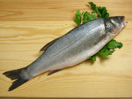 Sea bass on the cutting board with parsley