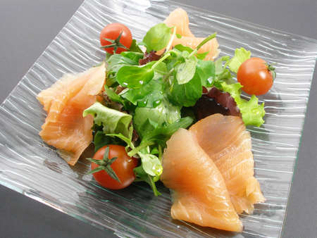Salmon apetizer salad in a glass plate