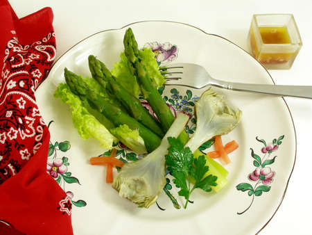 Green asparagus and artichoke served on a platter Stock Photo