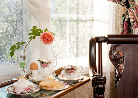 breakfast room: Breakfast - room service. Vintage  antique style interior design. Matching patterns of tableware and the curtains. Fine bone china. Cross stitch tea tray. Tea room. Stock Photo