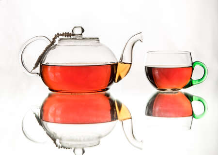 teacups: Rosy black tea in two glass teacups, green handle. Afternoon tea at home. Isolated in white background.