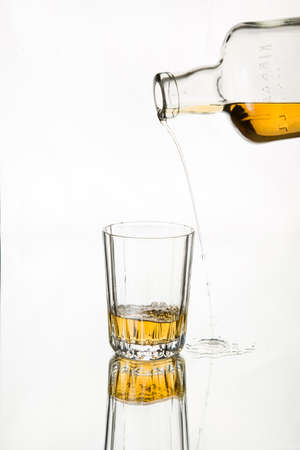 drink responsibly: Drink responsibly; Drink aware; Dont drink and drive. Pouring whiskey missed the glass. Isolated, white background. Art in food and drink. Stock Photo
