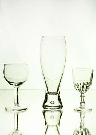sediento: Vino y cerveza vaso, a la luz de neón verde, fondo blanco. Sediento de bebidas. Arte en la comida y la bebida.