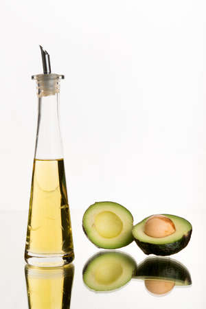 gezond koken: Avocado and avocado oil, white background. Clear bottle and container. Healthy cooking oils.  Art in food and drink.