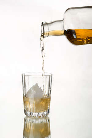whiskey on the rocks: Single malt Scotch  whiskey pouring into glass, transparent glass and bottle. Isolated. White background. Whiskey on the rocks.