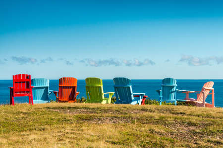 cape: 7 Colorful chairs, red, green, blue, green,  by the sea. Early retirement. Vacation time. Financial freedom. Peace of mind. Pleasant Bay, Cape Breton, Nova Scotia, Canada