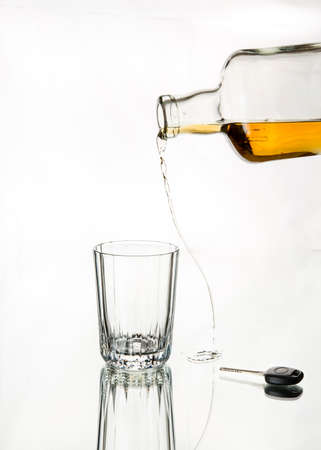 drink responsibly: Pouring whiskey missed the glass. Isolated, car key in the frame, white background. Drink responsibly; Drink aware; Dont drink and drive.
