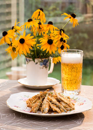 fresh water smelt: Baked smelt with bread crumbs and crushed nuts, on antique English plate. Indian pale ale IPA beer and bouquet in vintage fine bone china mug. Garden in the background. Stock Photo