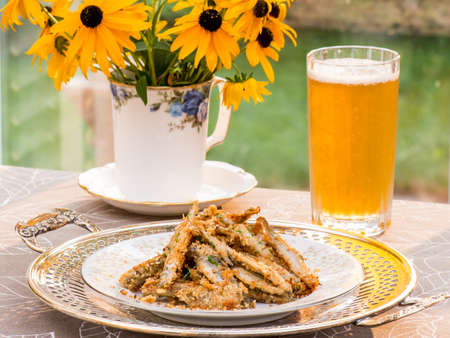 fresh water smelt: Baked smelt with bread crumbs and crushed nuts, on antique silver plate. Indian pale ale IPA beer and bouquet in vintage fine bone china mug. Garden in the background.