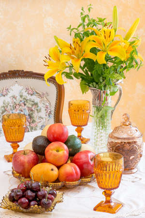 dignity: Antique  retro style afternoon tea table. Fruits and nuts in light brown Depression glassware. Dignity and elegance from the difficult time of America in the 1930s. Tablescape. Stock Photo