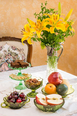difficult lives: Antique  retro style afternoon tea table. Fruits and nuts in light brown Depression glassware. Dignity and elegance from the difficult time of America in the 1930s. Tablescape. Stock Photo