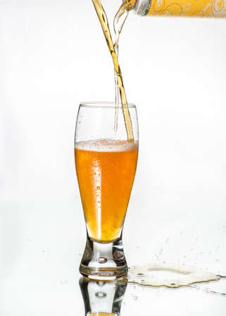 weiss: Mixing beers of different color and characteristics.  Unfiltered golden ale and weiss beer. On glass table, isolated in white background. Cold beer with condensed water on glass.. Craft beer. Stock Photo