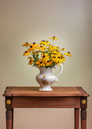 antique vase: Bouquet of yellow daisy matching the gold plated daisy hardware on an antique French Louis XVI style mahogany table from the 1930s. Black eyed Susan, Rudbeckia hirta in vintage vase. Retro style home.