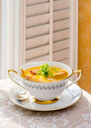 antique asian: Asian fusion chicken soup,  in antiquevintage fine bone china cream soup bowl tableware. Antique sterling silver spoon. Prepared with  Prosciutto ham, free range chicken, clear soup. Stock Photo