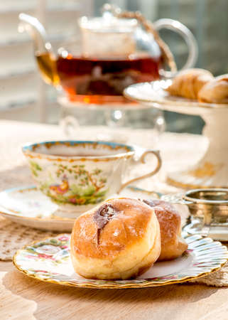 chantilly: Chantilly cream stuffed buns on afternoon tea table, in warm sunlight. Antique English fine bone china teacups, plates and cake stand, silver antique tea strainer. Stock Photo