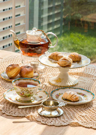 tea table: Sfogliatelle cake and Chantilly cream stuffed buns on afternoon tea table in the garden, in warm sunlight. Antique English fine bone china teacups, plates and cake stand, silver antique tea strainer.