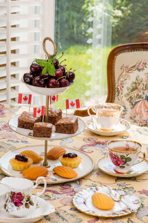 tea table: Celebrating Canada Day, Civic Holiday. Afternoon tea table setting Tablescaping.  Warm late afternoon sunlight. Antique English teacups.