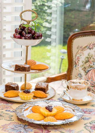 the madeleine: Retro  Vintage style tea room, vintage home interior. Afternoon tea time. Antique bone china teacups and antique furniture. madeleine cake, brownie.