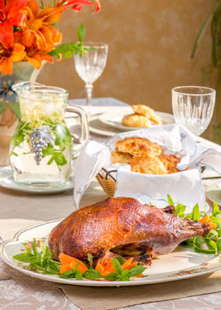 duck: Smoked duck on a vintage plate on summer time dinner table. Bouquet in vintage English vase. Bird shaped napkin rings. In bright natural light. Herbal tea in vintage jar. Roasted duck.