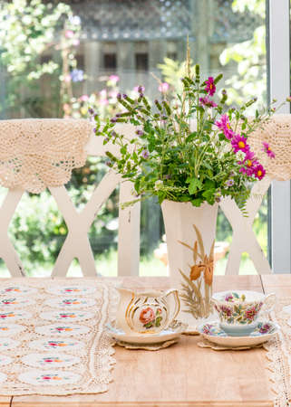 antique vase: French country style afternoon tea table in the garden. Antique  vintage English fine bone china vase, tea cup and creamer. Hand knit lace table cloth.