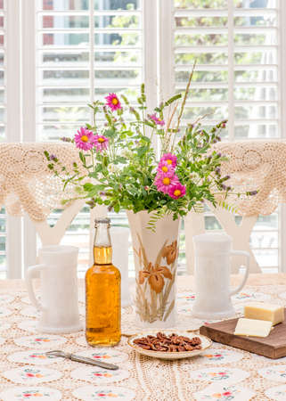 back cloth: Beer on French country style table. Antique  vintage white glass beer mugs; hand knit lace table cloth, rustic chairs and table, cheese and pecan on table. California shutters in the back. Stock Photo