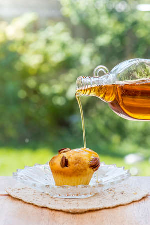 maple trees: Maple Syrup on muffin. Canada No. 1 light maple syrup, organic. Afternoon tea in the garden. Stock Photo