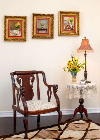 living style: Antique  Retro style living room. Antique armchair, wine table, lamp, ottoman. Fresh flower in English hand painted vase. Hand knit cushion in the chair. English fine china teacup.
