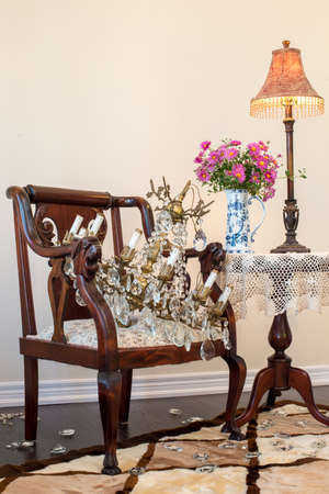 antique vase: Antique brass chandelier on antique armchair. Daisy bouquet in English china vase. Rug of sheep skin,