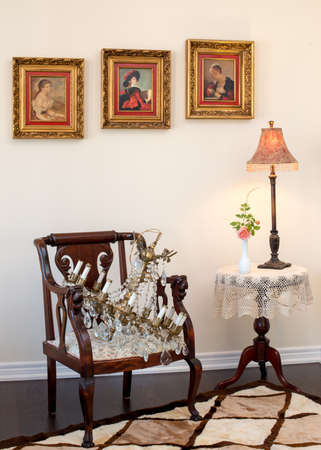 sheep skin: Collectible antique brass crystal chandelier on antique armchair. Fresh cut pink rose in white antique Depression glass vase. Rug of sheep skin. Antique  Retro style living room.