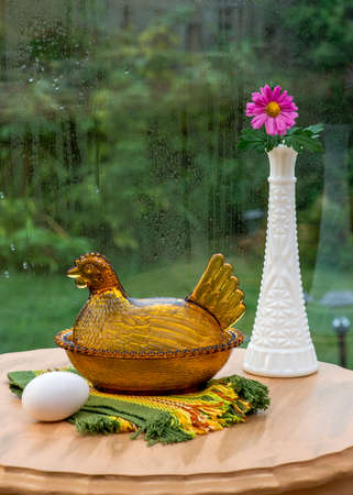 antique vase: Prepared for the rainy day. Antique depression glass hen shaped bowl. Flower in white antique glass vase. Rain on window pane. Stock Photo