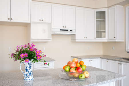 house prices: New house closing day. Empty kitchen. Fruits and flower on granite counter top. White cabinet. Stock Photo