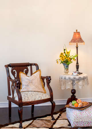 room for text: Antique  Retro style living room.  Space for text. Antique armchair, wine table, lamp, ottoman. Fresh flower in English hand painted vase.