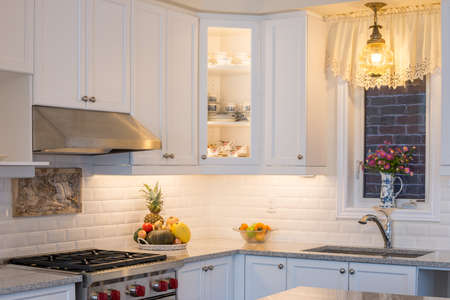 cabinets: New kitchen with touch of retro. Professional style gas range and hood, white cabinet,  antique ceiling lamp, antique vase and fine bone china teacups in cabinets. Interior design .
