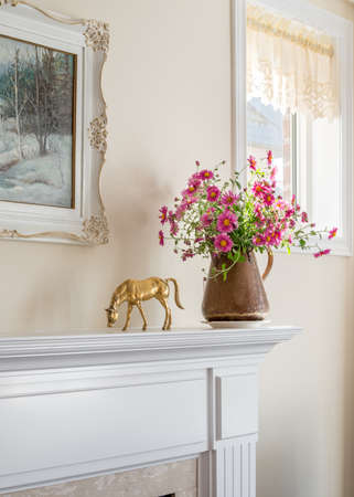 antique vase: Mantelpiece decoration. Antique copper vase on fireplace mantle in a new house. Morning sunlight.
