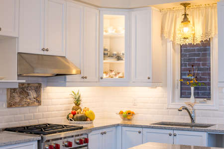 antique vase: New kitchen with touch of retro. Professional style gas range and hood, white cabinet,  antique ceiling lamp, antique vase and fine bone china teacups in cabinets. Interior design .